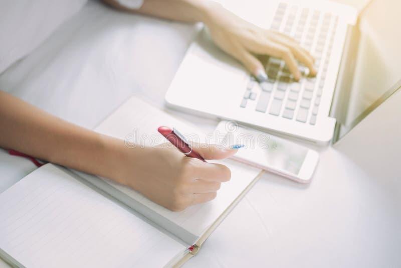 Azjatyckie biznesowe kobiety używa notatnika dla worek i ono uśmiecha się szczęśliwy obrazy stock