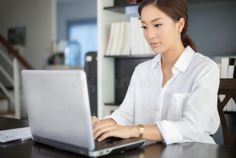 Azjatyckie biznesowe kobiety używa notatnika dla worek i ono uśmiecha się szczęśliwy zdjęcie royalty free