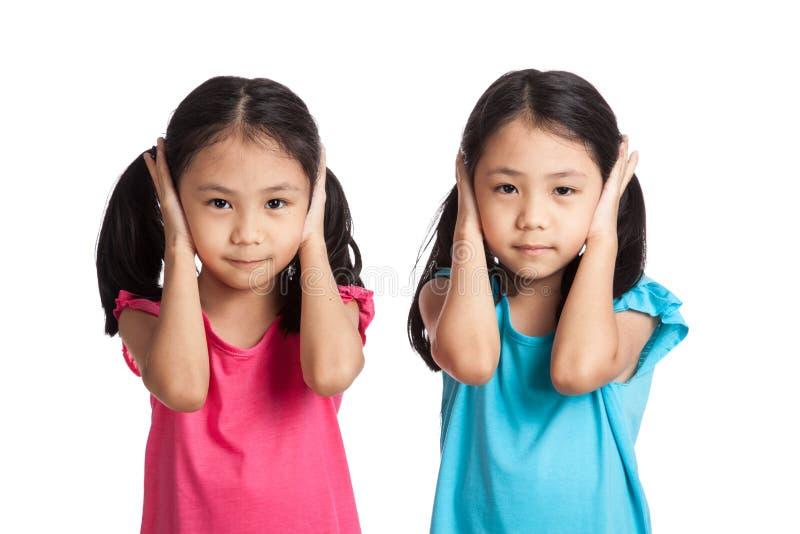 Azjatyckie bliźniak dziewczyny zakrywają ich ucho obraz stock