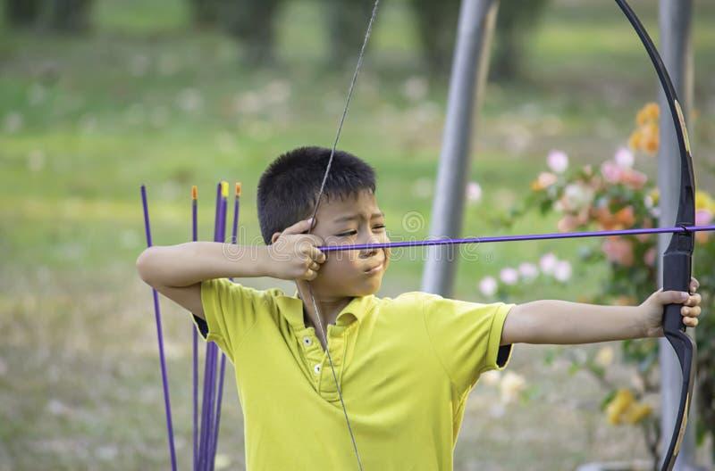 Azjatyckie chłopiec są łucznicze w obozowej przygodzie zdjęcia royalty free