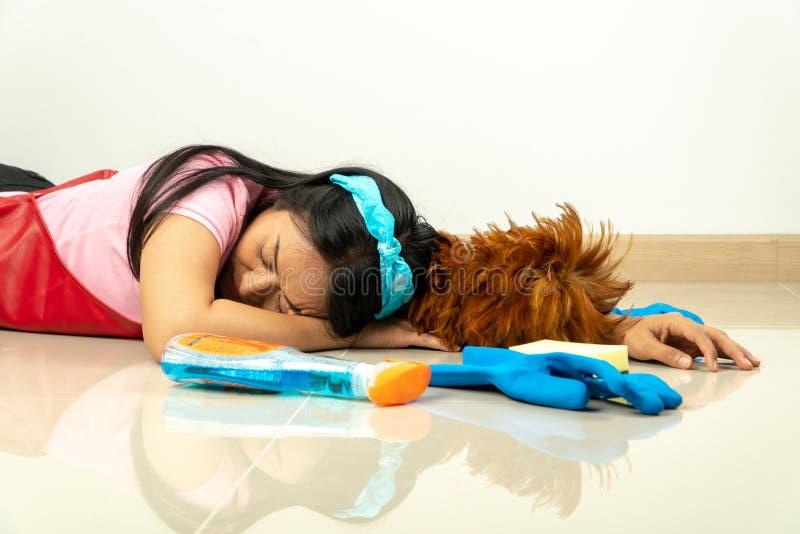Azjatyckie gospodynie domowe kłamają na podłodze należnej zmęczenie od gospodarstwo domowe obowiązek domowy Z różnorodnym czyści  zdjęcia royalty free