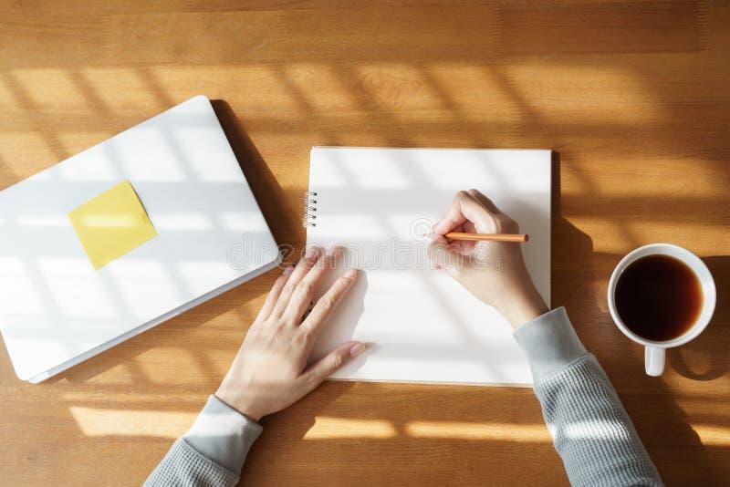 Azjatyckie kobiety biorą notatki na drewnianym stole z kawowymi kubkami i laptopami w domu zdjęcie stock