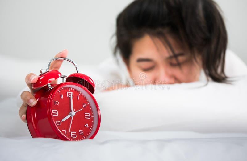 Azjatyckie kobiety budzili się od sen ona ręka chwyt przy zegarem I zdjęcia royalty free