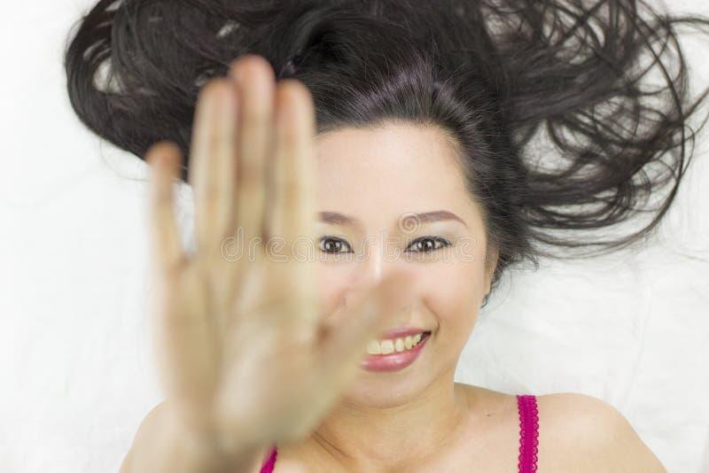 Azjatyckie kobiety kłama na ziemi z czarny długie włosy działający uśmiechu, szczęśliwego i seansu przerwy gest, obrazy stock