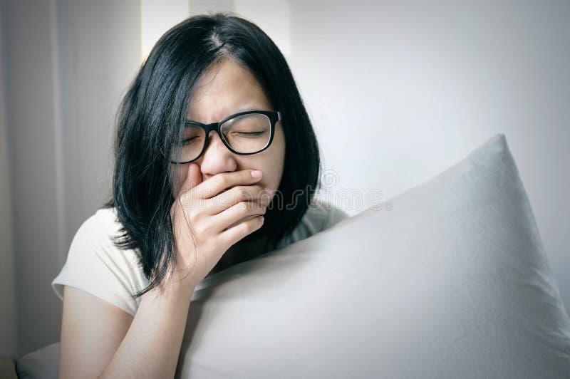 Azjatyckie kobiety kichają i ka na jej łóżku fotografia royalty free