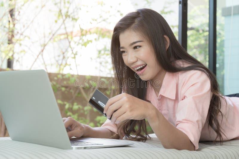 Azjatyckie kobiety są odpoczynkowe na kanapie w domu i robią zakupy onlin obraz royalty free