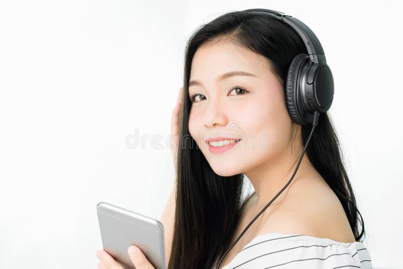 Azjatyckie kobiety słuchają muzyka od czarnych hełmofonów W wygodnym i dobrym nastroju obraz stock