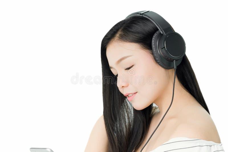 Azjatyckie kobiety słuchają muzyka od czarnych hełmofonów W wygodnym i dobrym nastroju obrazy royalty free