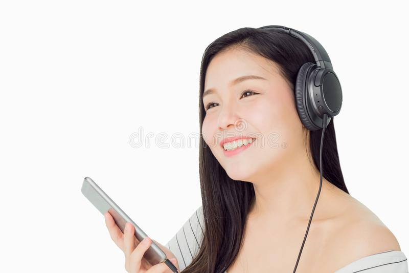 Azjatyckie kobiety słuchają muzyka od czarnych hełmofonów W wygodnym i dobrym nastroju fotografia royalty free