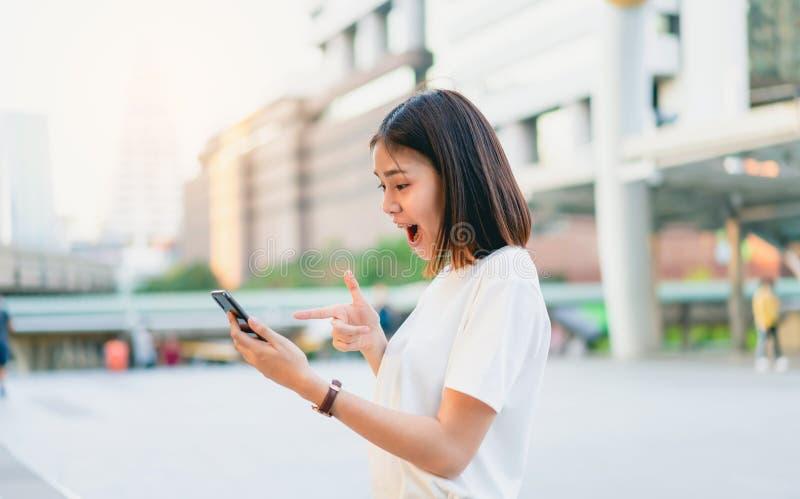 Azjatyckie kobiety szczęśliwy ono uśmiecha się i trzyma mądrze telefon z zadziwiający dla sukcesu obraz royalty free