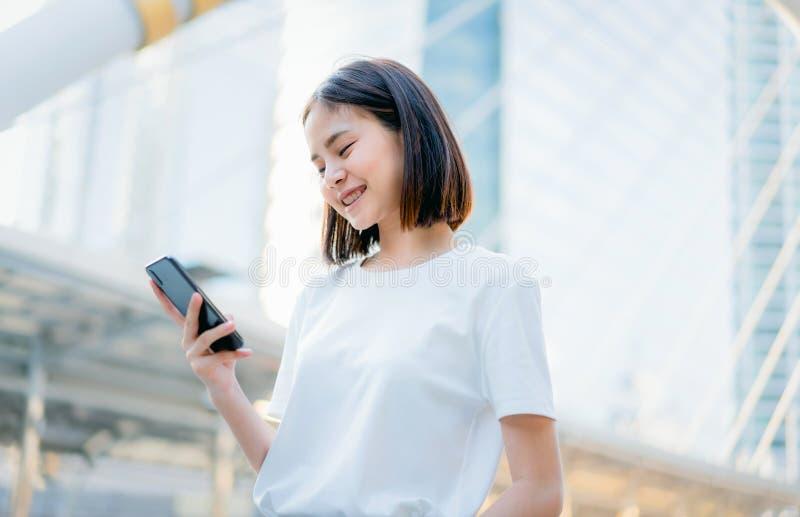 Azjatyckie kobiety szczęśliwy ono uśmiecha się i używa smartphone obraz stock