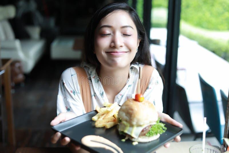 Azjatyckie kobiety uśmiechnięte, szczęśliwe i cieszyć się jedzący hamburger przy c obraz royalty free