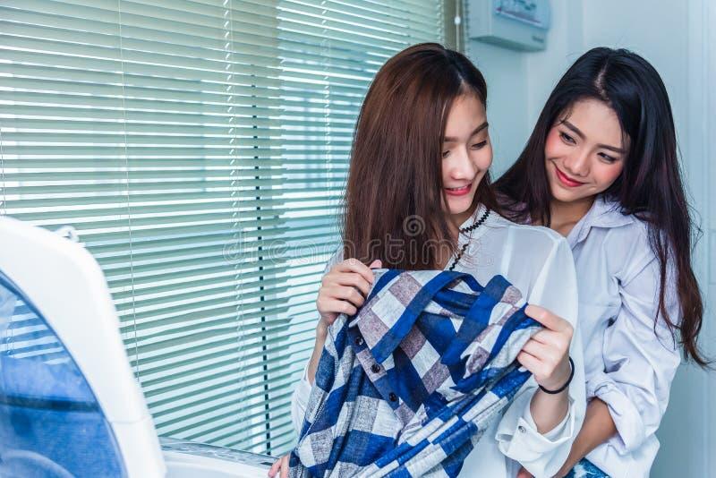 Azjatyckie par kobiety robi sprzątaniu i obowiązek domowy wpólnie przed i w pralnianym pokoju pralką i ładowań ubraniami zdjęcia royalty free