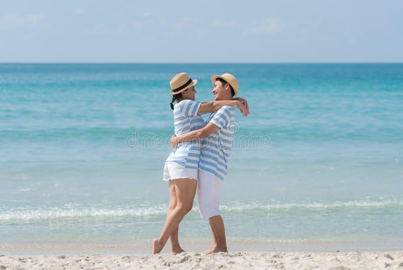 Azjatyckie pary otaczają się i patrzą na siebie szczęśliwie na plaży fotografia stock