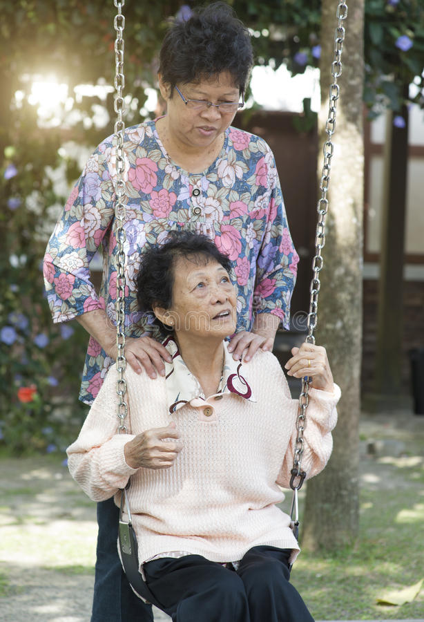 Azjatyckie starsze kobiety bawić się huśtawkę przy plenerowym boiskiem zdjęcia stock