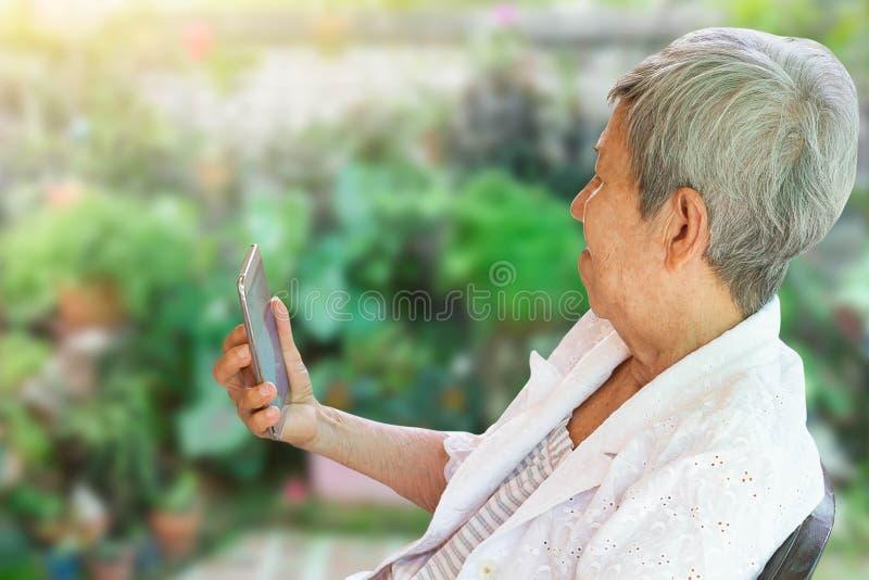 Azjatyckie starsze kobiety siedzi w ogrodowym mienia smartphone obrazy royalty free