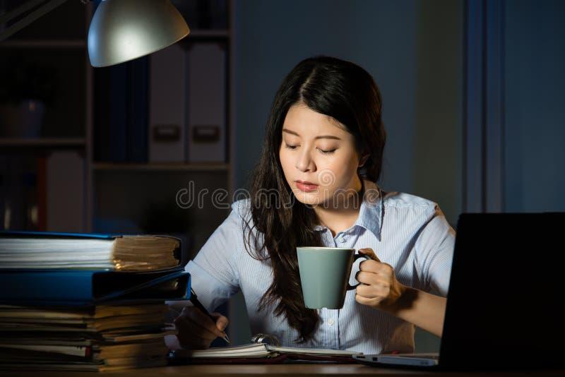 Azjatyckiego biznesowej kobiety napoju kawowy pracujący nadgodzinowy nocny fotografia stock
