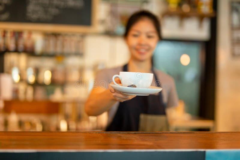 Azjatyckiego kobiety barista słuzyć filiżanka klient przy kawiarnią obraz royalty free