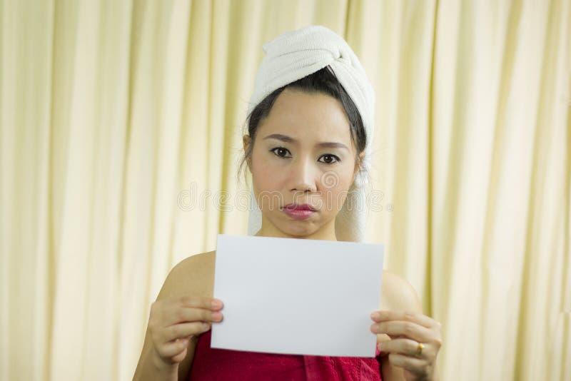 Azjatyckiego kobiety mienia pusty pusty sztandar i działanie jest ubranym spódnicę zakrywać jej pierś po obmycie włosy, Zaw obraz stock
