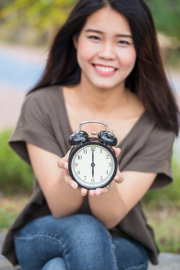 Azjatyckiego kobiety ręki chwyta przedstawienia retro zegarowi czasy przy 6 o ` zegarem zdjęcie royalty free