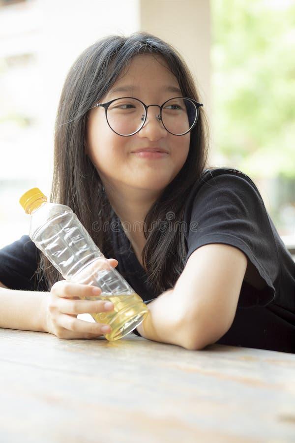 Azjatyckiego nastolatka uśmiechnięta twarz trzyma pastic butelkę w ręce obraz royalty free