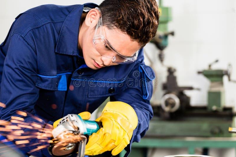 Azjatyckiego pracownika szlifierski metal w zakładzie produkcyjnym obrazy stock
