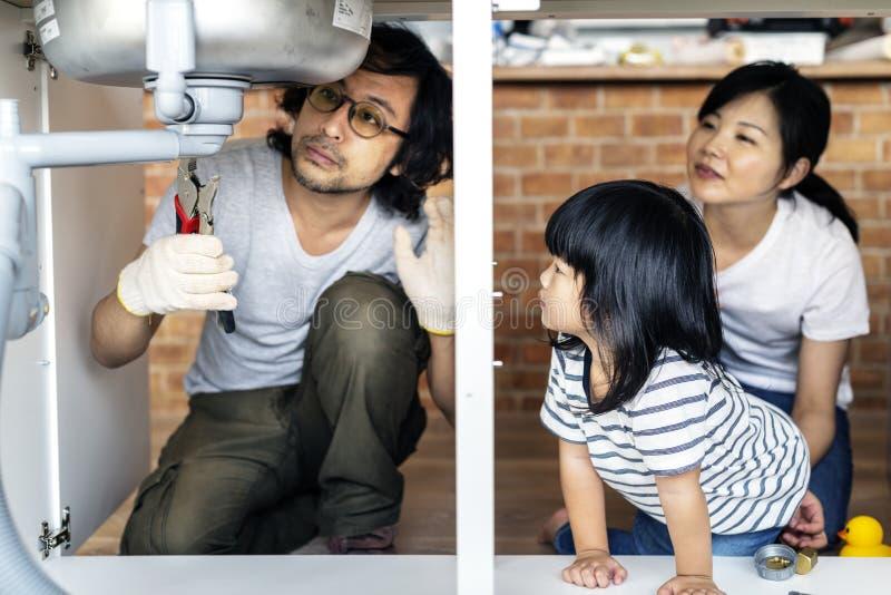 Azjatyckiego rodzinnego naprawiania kuchenny zlew obrazy royalty free