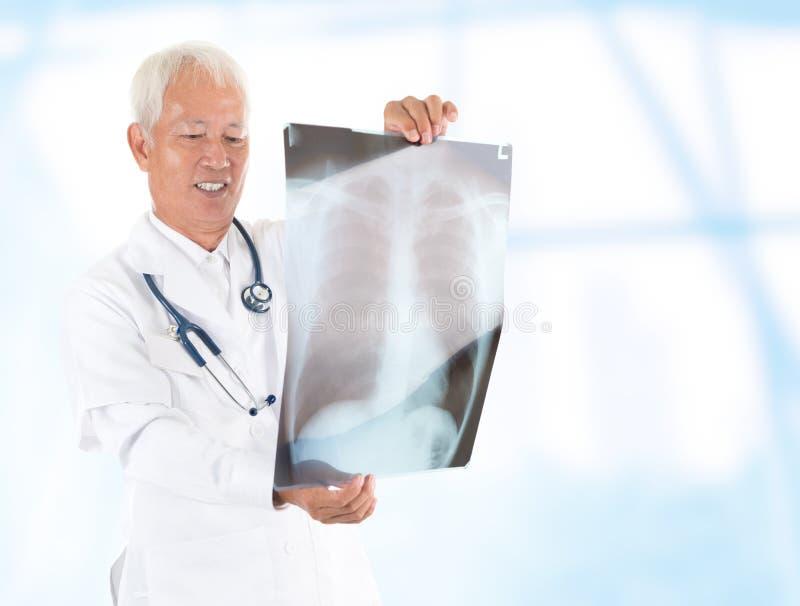 Azjatyckiego seniora doktorski sprawdzać na promieniowanie rentgenowskie wizerunku zdjęcie stock