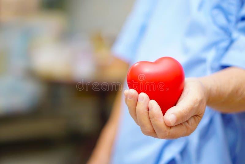 Azjatyckiego seniora lub starszego starej damy kobiety cierpliwego mienia czerwony serce w jej ręce zdjęcia royalty free