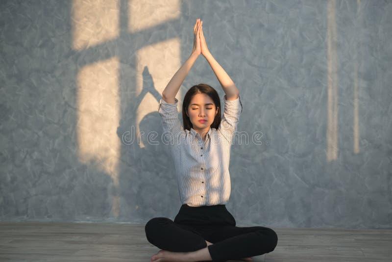 Azjatyckiej biznesowej dziewczyny ćwiczy joga w biurze pojęcie real obrazy royalty free