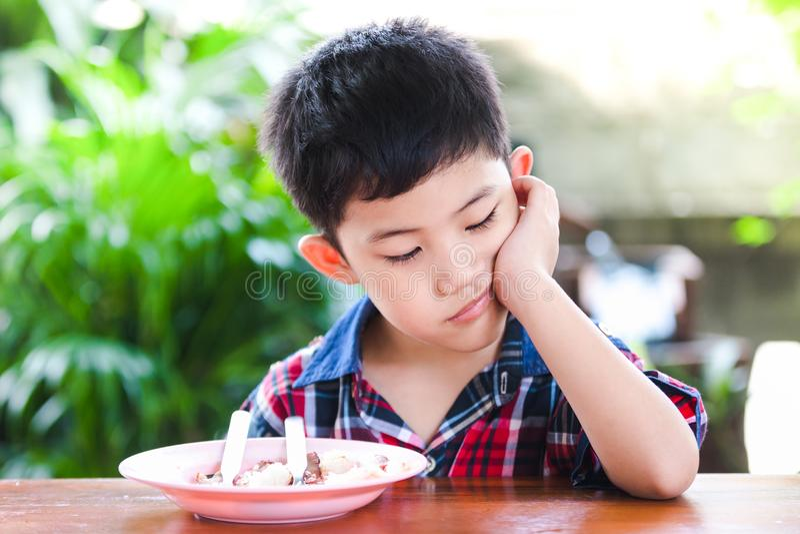 Azjatyckiej chłopiec nudny łasowanie z ryżowym jedzeniem zdjęcia royalty free