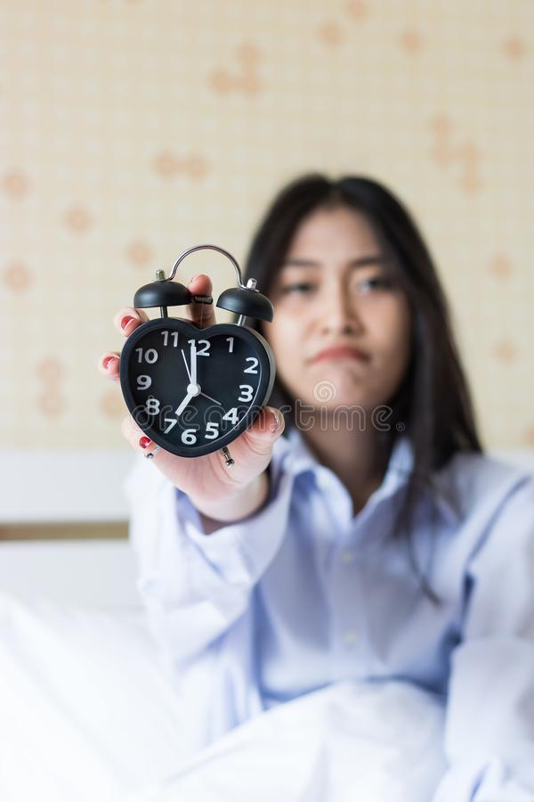 Azjatyckiej dziewczyny przyglądający budzik po budzić się up póżno zdjęcia stock