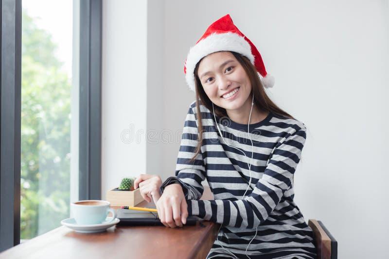 Azjatyckiej dziewczyny uśmiechnięty obsiadanie w sklep z kawą, kobieta jest ubranym Santa Cl obrazy stock