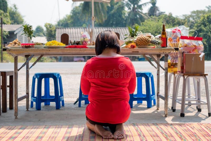 Azjatyckiej kobiety czerwony koszulowy obsiadanie i modlenie antenat z posiłkiem, obrazy royalty free