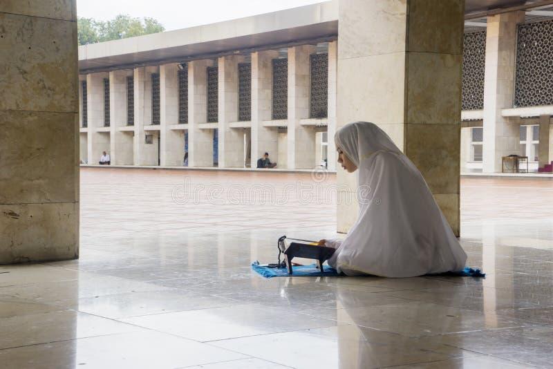 Azjatyckiej kobiety czytelniczy koran w Istiqlal meczecie zdjęcie royalty free