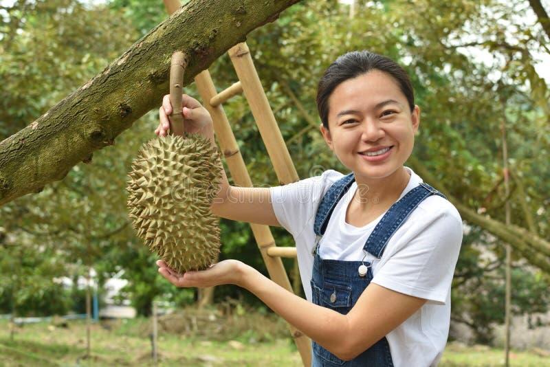 Azjatyckiej kobiety mienia średniorolny Durian jest królewiątkiem owoc w Tajlandia obraz stock