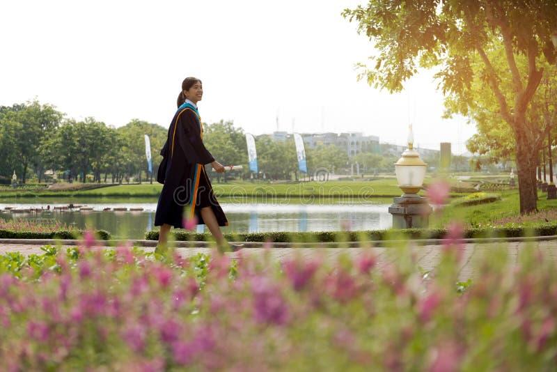 Azjatyckiej kobiety szczęśliwy Kończy studia chodzić z dużym uśmiechem zdjęcia royalty free