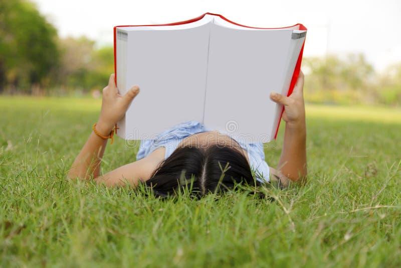 Dziewczyny czytelnicza książka w parku obrazy stock