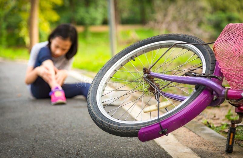 Azjatyckiej małej dziewczynki siedzący puszek na drodze z drobną bolesną noga bólu opłatą spada rowerowy wypadek roweru spadek pr zdjęcie royalty free