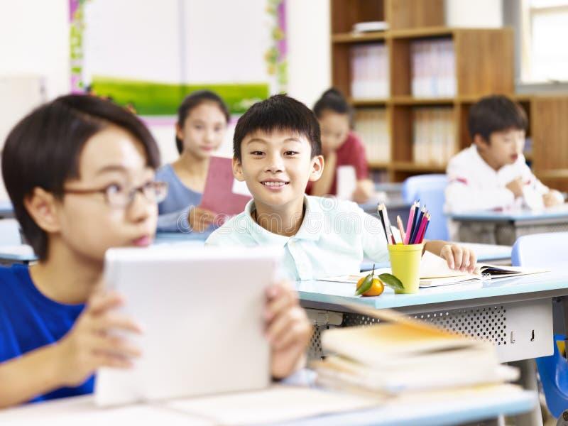 Azjatyckiej szkoły podstawowej studencka używa pastylka w sala lekcyjnej zdjęcia stock