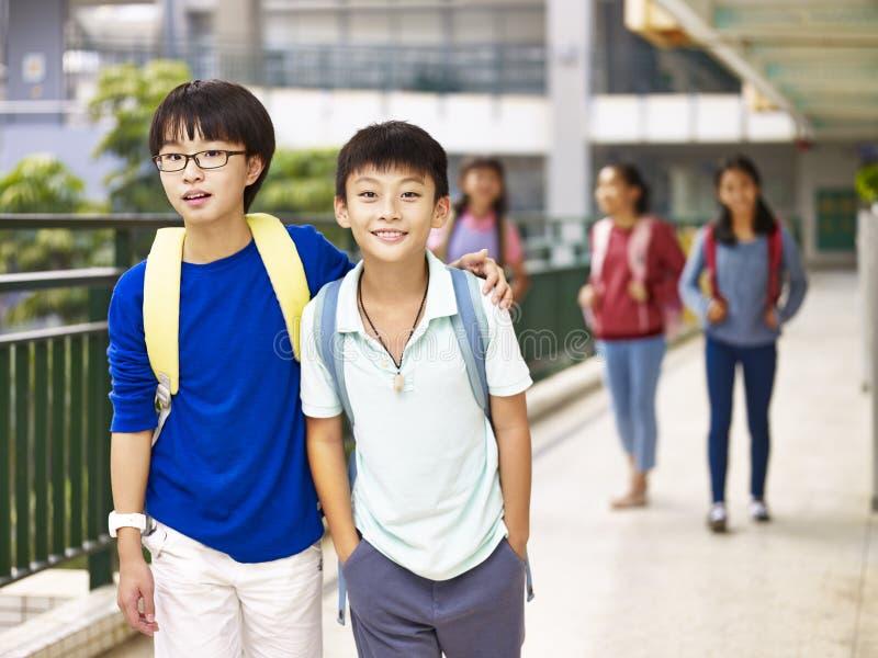 Azjatyckiej szkoły podstawowej studencki odprowadzenie na kampusie obraz royalty free