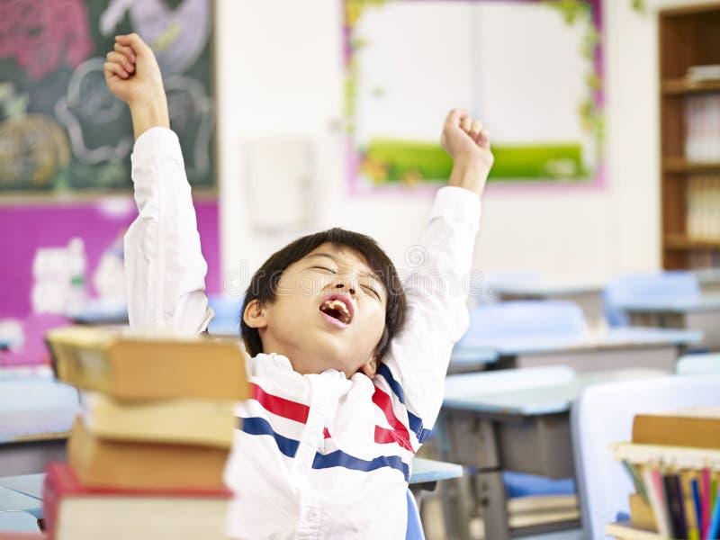 Azjatyckiej szkoły podstawowej studencki rozciąganie w sala lekcyjnej fotografia royalty free