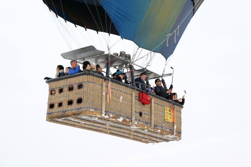 Azjatyckiej turysta grupy gorącego powietrza balonu inside kosz i latanie nad czarodziejskimi kominami zdjęcie stock
