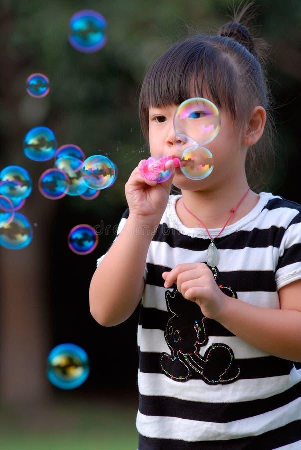 azjatykci dmuchanie gulgocze dziecka bawić się obraz stock