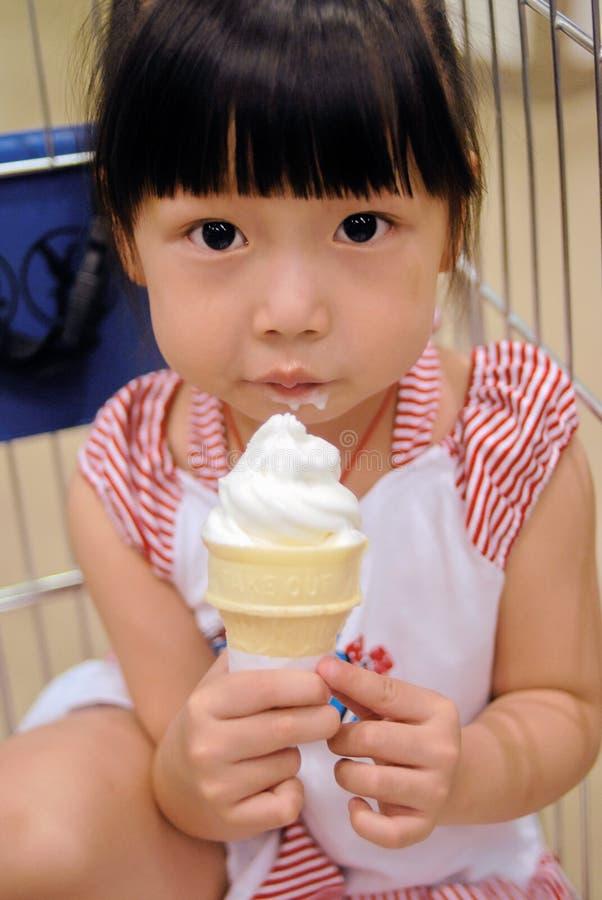 azjatykci dziecka śmietanki łasowania lód fotografia royalty free