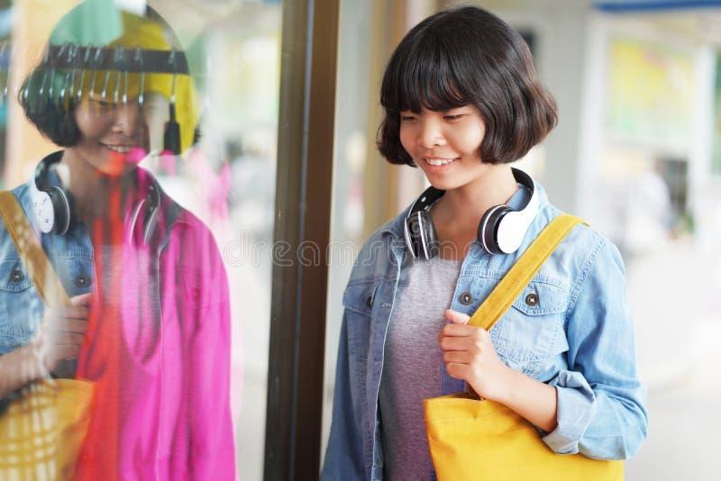 azjatykci kobieta zakupy z duży ciężar torbą i słuchawki przyglądającym płótnem w sklepie fotografia stock