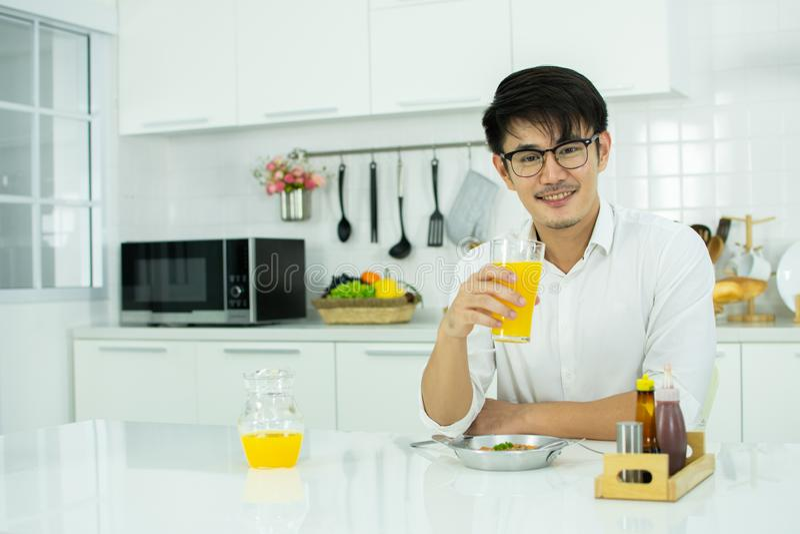 Azjatykci mężczyzna pije sok pomarańczowego w kuchni zdjęcie royalty free