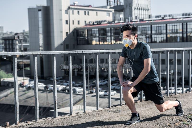 azjatykci nastoletni rozciąganie iść na piechotę w ochronnej masce na mostu powietrzu fotografia stock