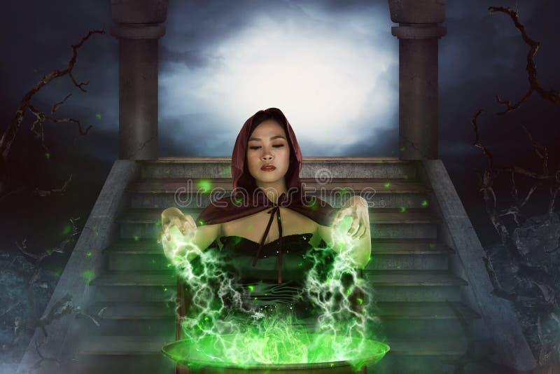 Azjatykcia czarownica z kocioł praktyki guślarstwem zdjęcia royalty free