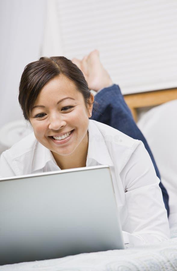 azjatykciego atrakcyjnego puszka laptopu łgarska kobieta fotografia royalty free